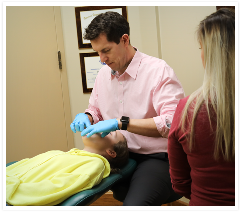 Picture of Dr Jason Aleman working with a patient